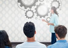Group of people in front of cog wheel graphics and woman speaker stock photos
