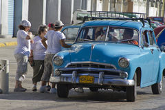 Group of people getting out ofold classic Cuban taxi car. Group of people getting out of old classic blue cuban car. Past international embargoes have meant Cuba Stock Image