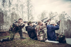 Group of people with guns aimed to the sky and prepared to make a shot Stock Image