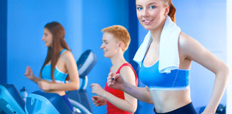 Group of people at the gym exercising on cross trainers Stock Photos