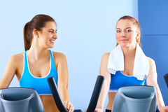 Group of people at the gym exercising on cross trainers.  Stock Photos