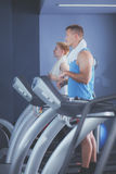 Group of people at the gym exercising on cross trainers.  Stock Photo