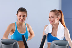 Group of people at the gym exercising on cross trainers.  Stock Images