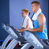 Group of people at the gym exercising on cross trainers.  Royalty Free Stock Images