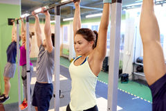 Group of people hanging at horizontal bar in gym Stock Images