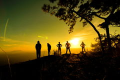 Group of people, Happy hiking standing on a cliff side with arms raised up Stock Photo