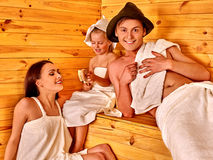 Group people in hat  at sauna. Family with one kid in hat  relaxing . Finnish sauna family Stock Photography