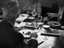 Group of people having dinner in the restaurant together grayscale royalty free stock images