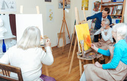 Group of people having lesson in painting school. Find yourself. Group of concentrated elderly delighted people having lesson while spending time in painting Royalty Free Stock Photography