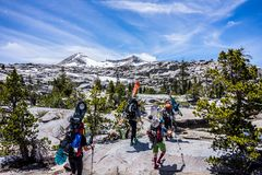 Group of People Hiking With Snowboards Under Blue Cloudy Sky Royalty Free Stock Photo