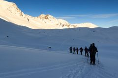 Group of people hiking on snowshoes and mountain snow panorama with blue sky in Stubai Alps Stock Photography