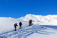 Group of people hiking on snowshoes and mountain snow panorama with blue sky in Stubai Alps. Austria royalty free stock image