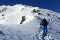 Group of people hiking on snowshoes and mountain snow panorama with summit cross in Stubai Alps Stock Image
