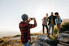 Group of people on hiking taking photographs. Young men taking picture of his friends while trekking in countryside during summer vacation. Group of people on royalty free stock photography