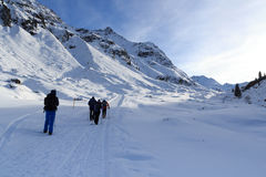 Group of people hiking on wintery snowy path and mountain panorama in Stubai Alps Stock Photography