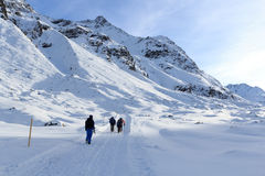 Group of people hiking on wintery snowy path and mountain panorama in Stubai Alps Royalty Free Stock Images