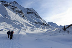 Group of people hiking on wintery snowy path and mountain panorama in Stubai Alps Stock Images
