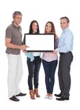Group of people holding billboard. Group Of Happy People Holding Billboard Together Over White Background stock photo