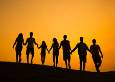 Group of People Holding Hands in Back lit Royalty Free Stock Image