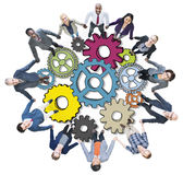 Group of People Holding Hands with Gear Symbols Royalty Free Stock Images