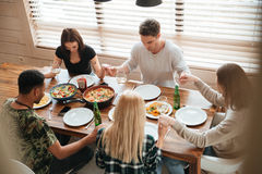 Group of people holding hands and praying at dinner table. Group of peaceful young people holding hands and praying at the dinner table royalty free stock photography