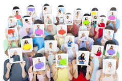Group of People Holding Tablets in Front of Faces. Multi-Ethnic Group of People Holding Tablets in Front of the Faces Royalty Free Stock Image