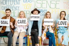 Group of people holding words on the topic of mental health. Group of diverse people sitting in a row and holding papers with various inscriptions on the topic royalty free stock image
