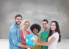 Group of people holding world globe in front of grey background Royalty Free Stock Photo