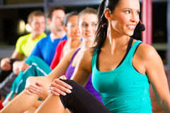 Group of people and instructor in gym stretching. Group of young people stretching in gym for better fitness led by instructor Royalty Free Stock Photo