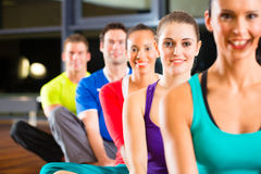 Group of people and instructor in gym stretching Royalty Free Stock Images