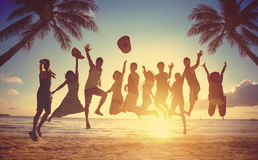 Group of people jumping at beach. Group of friends jumping against sunset Royalty Free Stock Images
