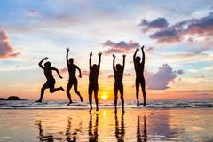 Group of people jumping on the beach at sunset, silhouettes of happy friends. On holidays stock photography