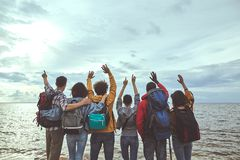 Group of people jumping with their hands up. Hello world. Portrait of friends greeting seaside holding their hands up royalty free stock image