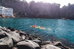 A group of people on kayaks are sailing. Italy, Sorrento, Meta Bay is popular tourist destination for sport kayaking and stock photography
