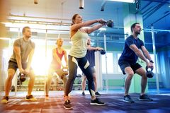 Group of people with kettlebells exercising in gym Royalty Free Stock Photos