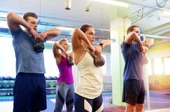 Group of people with kettlebells exercising in gym Stock Photo