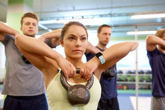 Group of people with kettlebells exercising in gym Royalty Free Stock Photo