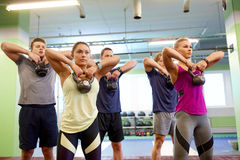 Group of people with kettlebells exercising in gym Stock Image