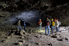 Group Of People In A Lava Tube Cave Royalty Free Stock Photos