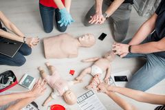 First aid training. Group of people learning how to make first aid heart compressions with dummies during the training indoors Stock Photography