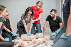 First aid training. Group of people learning how to make first aid heart compressions with dummies during the training indoors royalty free stock photos