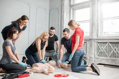 First aid training. Group of people learning how to make first aid heart compressions with dummies during the training indoors royalty free stock images