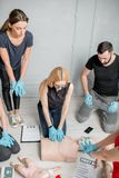 First aid training. Group of people learning how to make first aid heart compressions with dummies during the training indoors royalty free stock photography