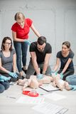 First aid training. Group of people learning how to make first aid heart compressions with dummies during the training indoors royalty free stock photo
