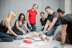 First aid training. Group of people learning how to make first aid heart compressions with dummies during the training indoors stock image