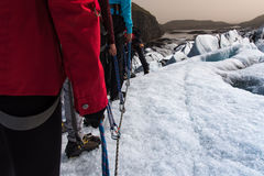 Group of people line up for climbing in Iceland. Glacier Royalty Free Stock Photography