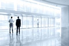 Group of people in the lobby business center and blue tonality Royalty Free Stock Photo