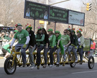 Group of people on a long bicycle greeting people at the Annual St Patrick's Day Parade Stock Images