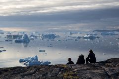 Group of people looking at icebergs in Rodebay, Greenland. Rodebay, Greenland - July 09, 2018: A group of people sitting and looking at icebergs. Rodebay, also royalty free stock photo