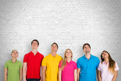 Group Of People Looking Up. Group Of Diverse Happy People Standing Against A Wall Looking Up Stock Photo